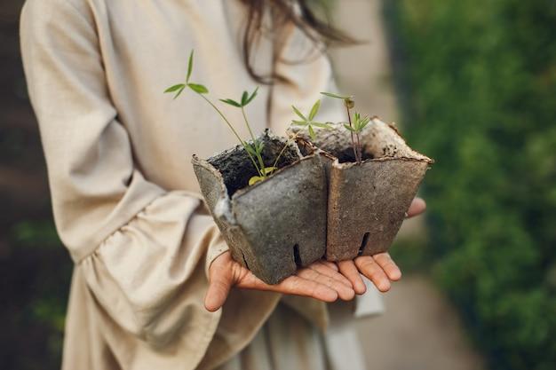Ragazza del bambino che tiene le piantine pronte per essere piantate nel terreno. piccolo giardiniere in un vestito marrone.