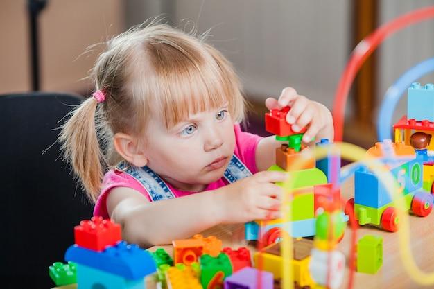 Ragazza del bambino con i giocattoli variopinti