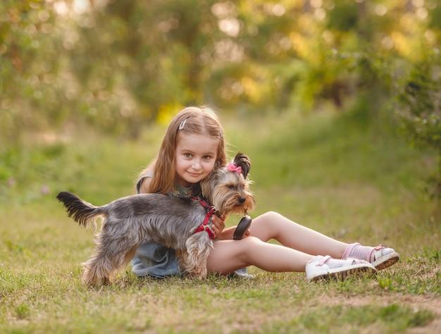 Ragazza del bambino con il suo piccolo cane dell'yorkshire terrier nel parco