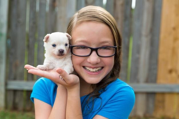 Ragazza del bambino con la chihuahua dell'animale domestico del cucciolo che gioca felice