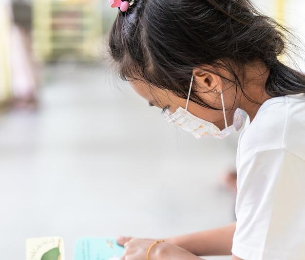 Ragazza del bambino con la maschera di protezione a scuola