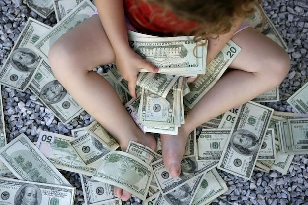 Ragazza del bambino con un sacco di banconote da un dollaro sul giardino di pietra