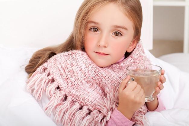 Ragazza del bambino con una tazza di tè caldo a letto