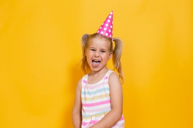 Ragazza del bambino di buon compleanno con due ponytales in protezione rosa su fondo giallo colorato che spinge la sua lingua.