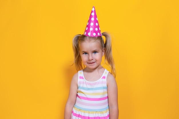 Ragazza del bambino di buon compleanno con due ponytales in protezione rosa su fondo giallo colorato.