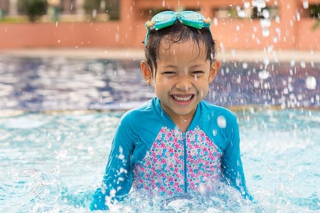 Ragazza del bambino di sorriso con gli occhiali di protezione nella piscina.