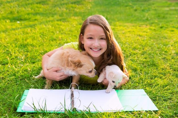 Ragazza del bambino e cucciolo di cane a fare i compiti che si trovano nel prato