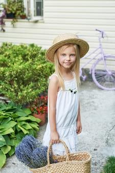 Ragazza del bambino in cappello con un cestino di lavanda nel giardino in estate