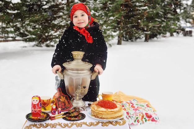 Ragazza del bambino in un cappotto di pelliccia e in una sciarpa in stile russo che tiene un grande samovar nelle mani di frittelle con caviale rosso