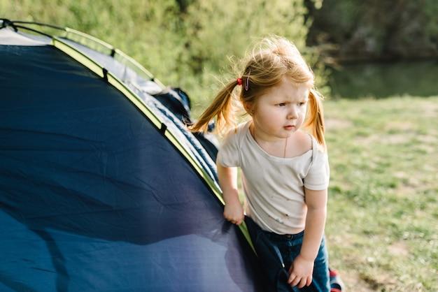 Ragazza del bambino in una campagna in una tenda in vacanza estiva sulla natura