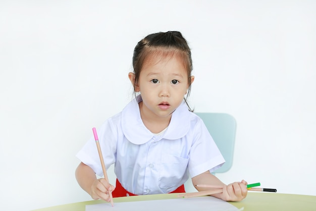 Ragazza del bambino in uniforme scolastica attingendo carta