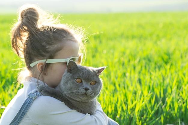 Ragazza del bambino piccolo divertendosi con il gatto, gatto sul giardino naturale