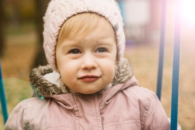 Ragazza del bambino soleggiata in cappello lavorato a maglia, guardando avanti