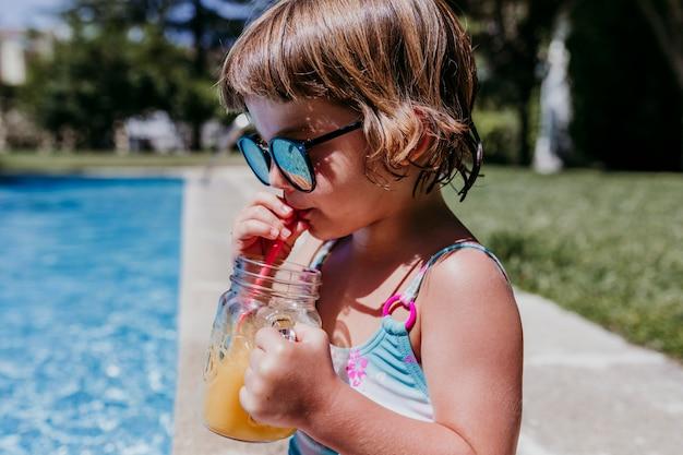Ragazza del bello bambino allo stagno che beve il succo di arancia sano e che si diverte all'aperto. concetto di estate e stile di vita