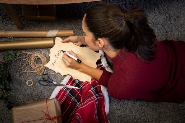 Ragazza del brunette che scrive una lettera per santa