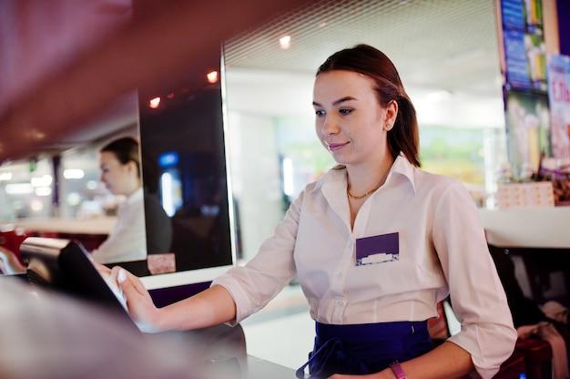 Ragazza del cameriere che lavora con il terminale di posizione o la cassa al caffè. concetto di persone e servizi