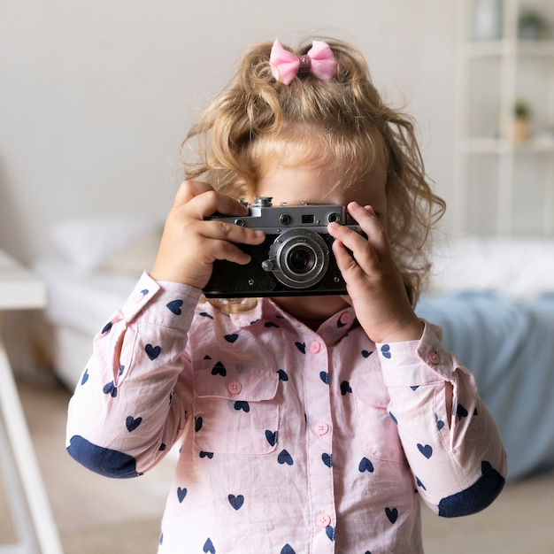 Ragazza del colpo medio che prende le foto con la macchina fotografica