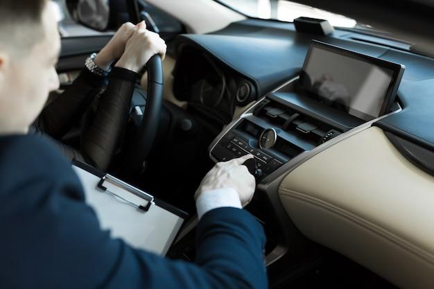 Ragazza del compratore e dell'agente dentro un'automobile in un concessionario auto. il venditore mostra l'auto al compratore.
