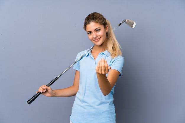 Ragazza del giocatore di golf dell'adolescente sopra la parete grigia che invita a venire