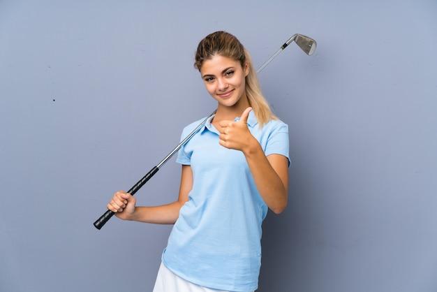 Ragazza del giocatore di golf dell'adolescente sopra la parete grigia con i pollici in su perché è successo qualcosa di buono