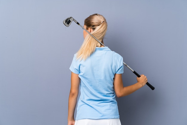 Ragazza del giocatore di golf dell'adolescente sopra la parete grigia