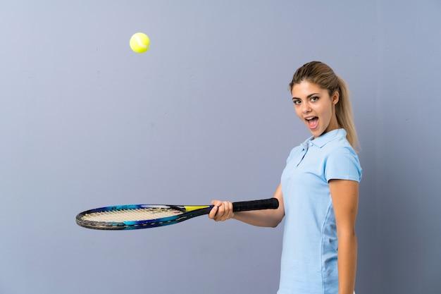 Ragazza del giocatore di tennis sulla parete grigia