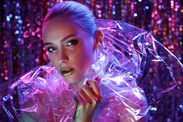 Ragazza del modello di alta moda alle luci al neon luminose variopinte che posano nello studio attraverso il film trasparente. ritratto di bella donna sexy in uv. art design trucco colorato.