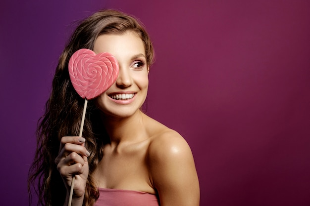 Ragazza del modello di moda con il cuore di san valentino, concetto di amore, giovane donna sorridente