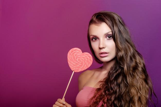 Ragazza del modello di moda con il cuore di san valentino, concetto di amore, giovane donna