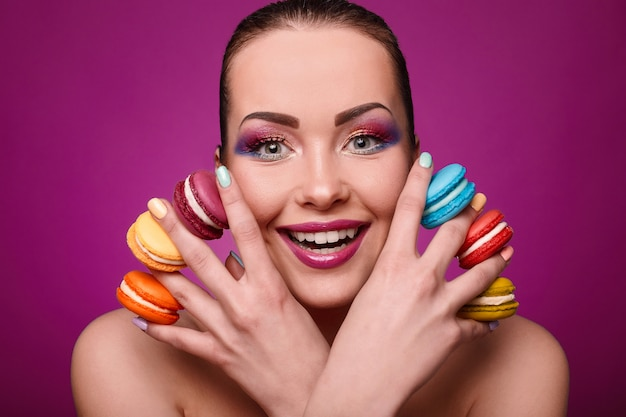 Ragazza del modello di moda di fascino di bellezza con trucco colorato e amaretti.