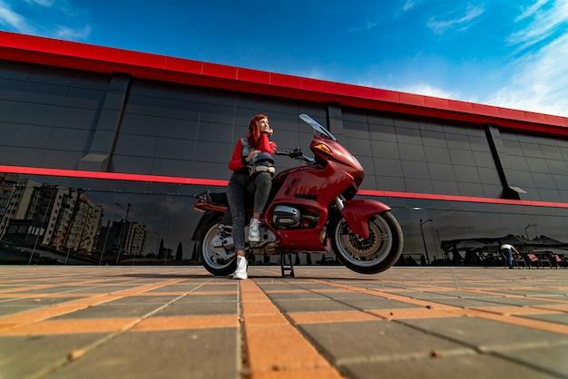 Ragazza del motociclista che si siede sulla moto custom vintage