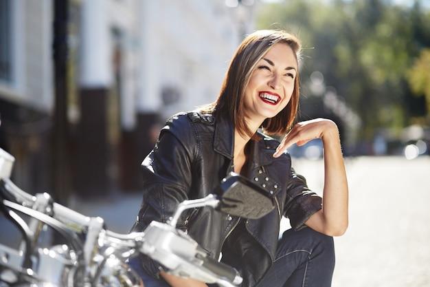 Ragazza del motociclista in una giacca di pelle su una moto
