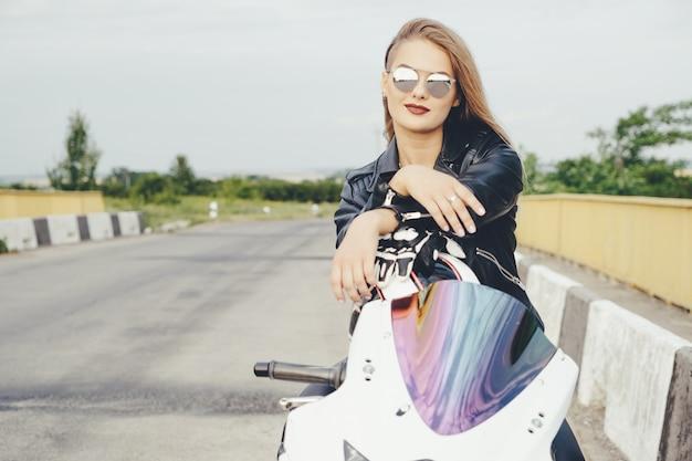 Ragazza del motociclista in vestiti di cuoio su una moto