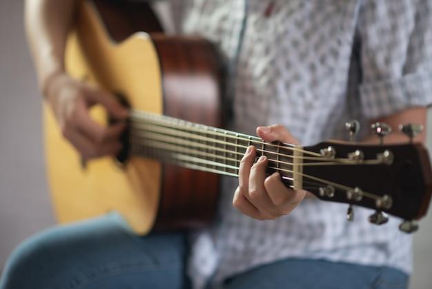Ragazza del musicista che gioca chitarra acustica