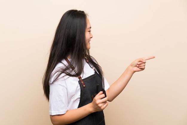 Ragazza del parrucchiere dell'adolescente che indica il lato per presentare un prodotto