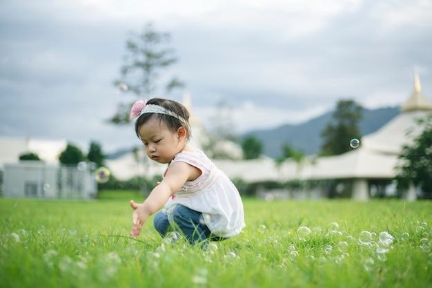 Ragazza del piccolo bambino che gioca con le bolle su erba verde all'aperto nel parco.
