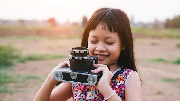 Ragazza del piccolo bambino che tiene la macchina da presa di medio formato e che prende foto del paesaggio di tramonto con il campo verde