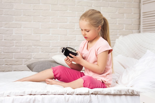 Ragazza del piccolo bambino in pigiama con l'orologio