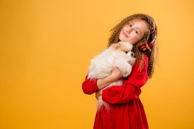 Ragazza del preteen che tiene un piccolo cane in mano