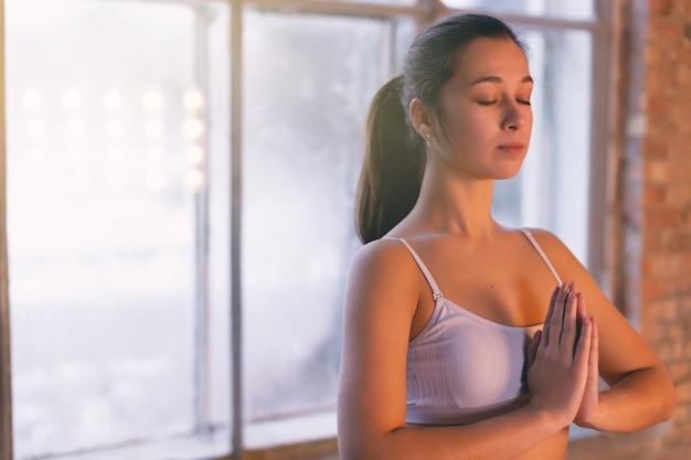 Ragazza del primo piano che fa yoga da solo nella stanza di yoga dalla finestra di mattina