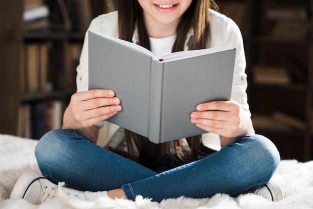 Ragazza del primo piano che legge un libro