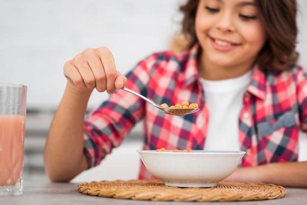 Ragazza del primo piano che mangia prima colazione a casa