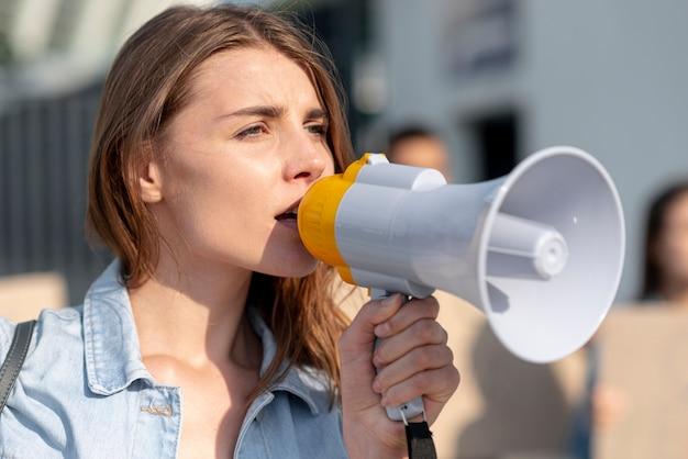 Ragazza del primo piano che protesta con il megafono