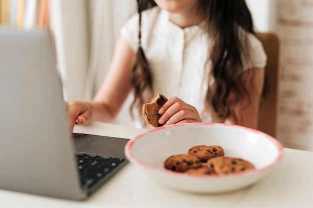 Ragazza del primo piano con il computer portatile e i biscotti