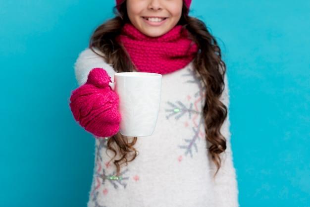 Ragazza del primo piano sull'inverno che beve tè caldo