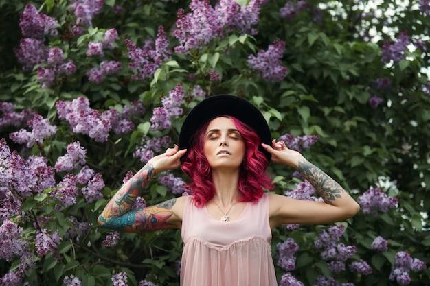 Ragazza del ritratto di bellezza della primavera bella con capelli rossi nel lillà di fioritura dei rami