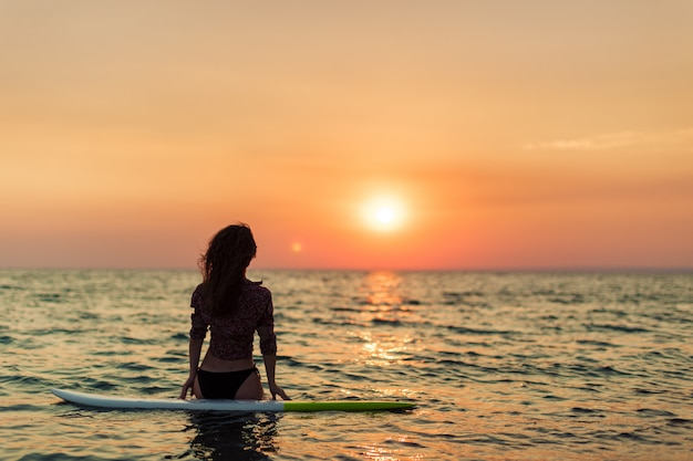 Ragazza del surfista che pratica il surfing guardando il tramonto della spiaggia dell'oceano
