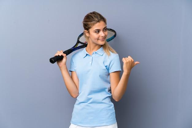 Ragazza del tennis dell'adolescente sopra la parete grigia che indica il lato per presentare un prodotto