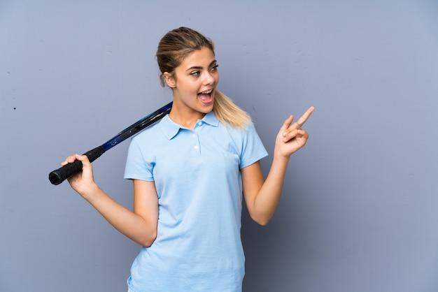 Ragazza del tennis dell'adolescente sopra la parete grigia sorpresa e indicando dito il lato