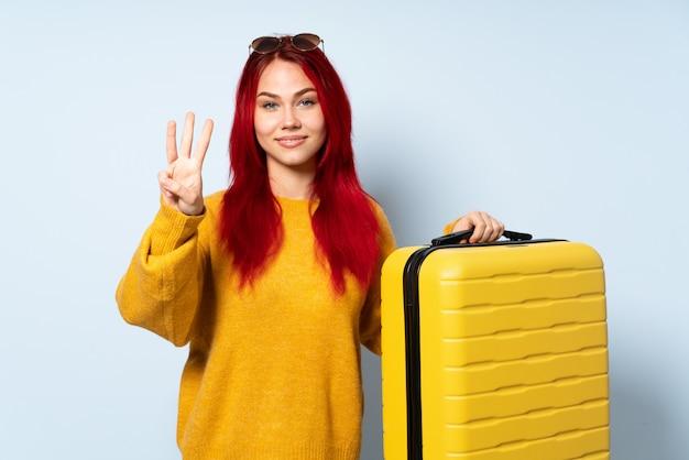 Ragazza del viaggiatore che giudica una valigia isolata su fondo blu felice e che conta tre con le dita
